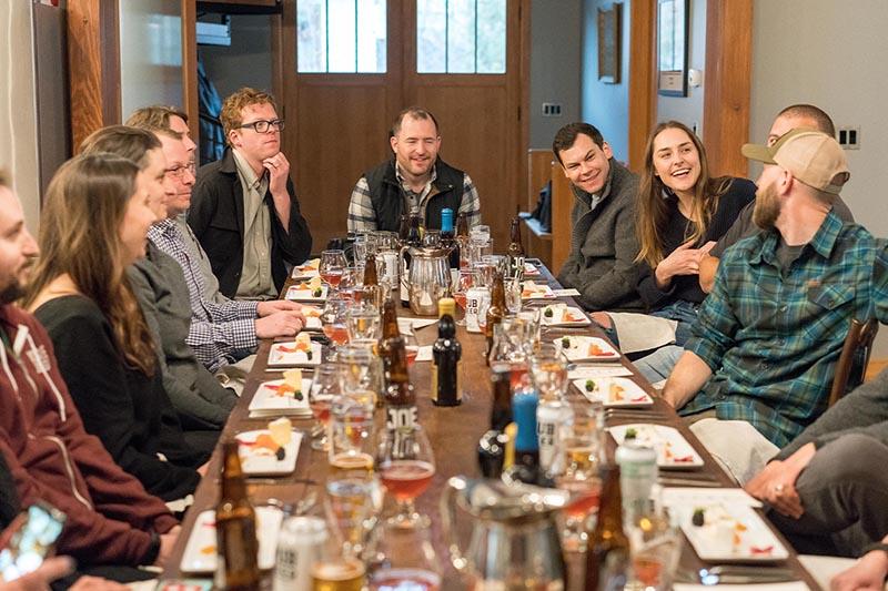 12 zichtbare mensen aan een rechthoekige tafel aan het praten met een bierje op tafel en een klein gerechtje dat ook al op tafel staat klaar om op te eten. Mensen zijn aan het praten en lachen.