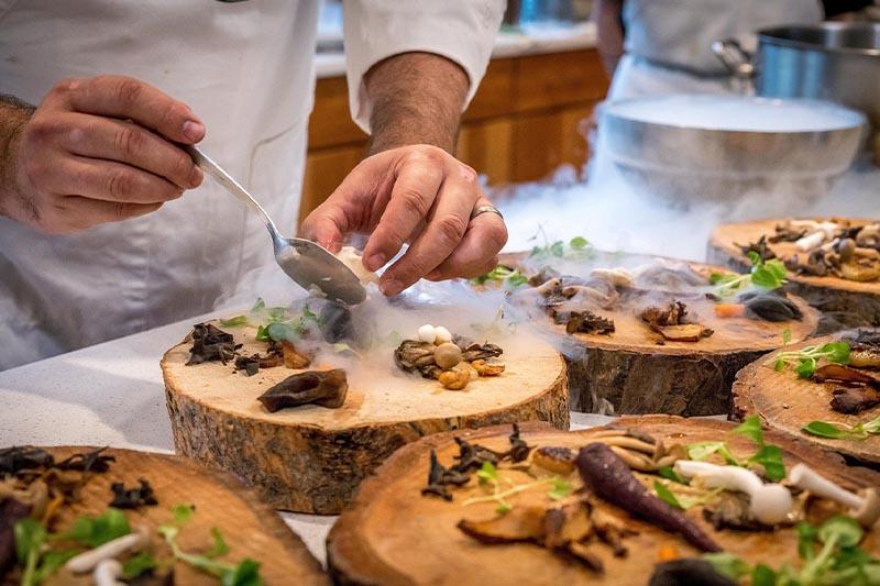 Workshop Foodpairing. Je ziet een kok met een lepel een ingrediënt op een blok hout leggen waar al verschillende paddestoelen op liggen en op de achtergrond staat er een kom met droogijs dat soort rook geeft.